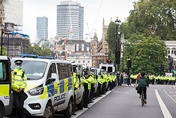 London, UK. 3rd September, 2020. Metropolitan Police officers prepare for the arrival in Parliament Square of climate activists from Extinction Rebellion attending a 'Carnival of Corruption' protest against the government's facilitation and funding of the fossil fuel industry. Extinction Rebellion activists are attending a series of September Rebellion protests around the UK to call on politicians to back the Climate and Ecological Emergency Bill (CEE Bill) which requires, among other measures, a serious plan to deal with the UK's share of emissions and to halt critical rises in global temperatures and for ordinary people to be involved in future environmental planning by means of a Citizens' Assembly.