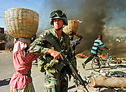 A US Army soldier assigned to the UN Force in Haiti keeps order at a roadblock of burning tires on Harry Truman Blvd in the port area of Port au Prince, Haiti, Monday, Feb. 12, 1996. Haiti will install newly elected president Rene Preval in a ceremony Wednesday. This will be the first peaceful transition of power in Haiti's history.  PHOTO BY JACK KURTZ