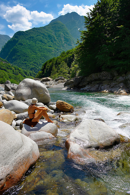 young lady sunbathing by a  rocky alpine foothills stream in the remote valley of Val Verzasca, near lavertezzo , Ticino .<br /> <br /> Visit our SWITZERLAND  & ALPS PHOTO COLLECTIONS for more  photos  to browse of  download or buy as prints https://funkystock.photoshelter.com/gallery-collection/Pictures-Images-of-Switzerland-Photos-of-Swiss-Alps-Landmark-Sites/C0000DPgRJMSrQ3U
