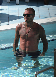 Shirtless David Beckham celebrates his new team, Inter Miami, as he has a few cocktails and takes a dip in the pool in Miami. The new team owner was seen indulging in a number of celebratory cocktails, conversing with a pretty brunette, photographing his teams new logo on the front page of the newspaper, and noshing on a burger and fries, in between taking dips in the pool to cool off. 06 Sep 2018 Pictured: David Beckham; Inter Miami; MLS Miami. Photo credit: MEGA TheMegaAgency.com +1 888 505 6342
