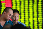 Investors monitor prices and make trades at a securities exchange house in Shanghai, China on 08 August 2011.  China's A shares had the biggest drop in a year following the global down turn as well as monetary tightening concerns in China.
