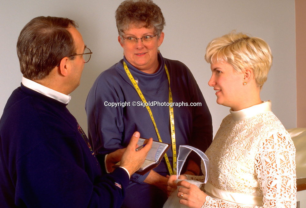 Dad and mom talking to bride age 50 and 21 after helping adjust wedding dress.  St Paul Minnesota USA