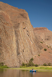 North America, United States, Oregon, John Day River, whitewater raft under huge columnar basalt rock formation