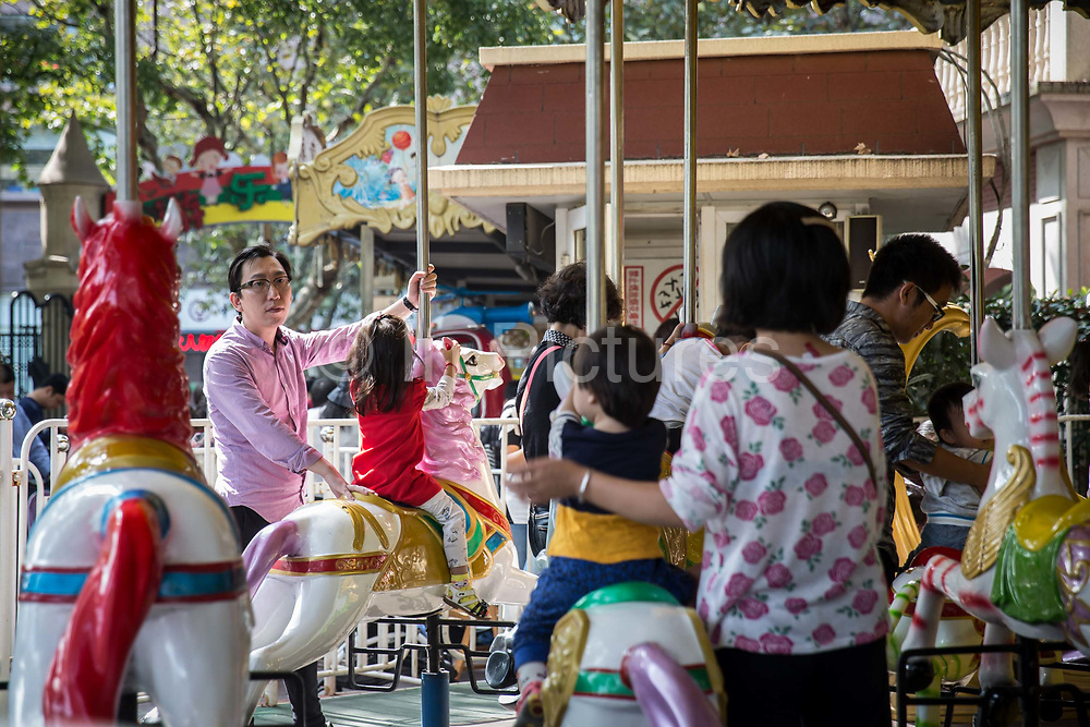 Families take rides on a carousel at Lu Xun Park in Shanghai, China, on Saturday, Oct. 24, 2015.