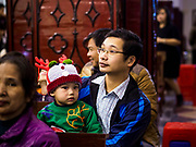 24 DECEMBER 2017 - HANOI, VIETNAM:  A man and his son wait for Christmas Eve services to start in St. Joseph's Cathedral in Hanoi. The commercial and gift giving aspect of Christmas is widely celebrated in Vietnam and Vietnam's 5+ million Catholics celebrate the religious aspects of Christmas.     PHOTO BY JACK KURTZ