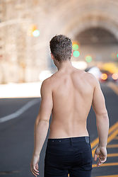 muscular shirtless man with back to camera in New York City