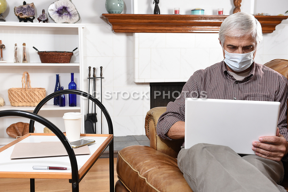 Man Wearing a Surgical Mask Working From Home On His Laptop
