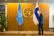 United Nations Protocol Assistant Roderick Santos, adjusts the flag of Finland prior to President  Sauli Niinisto,  entering the room.