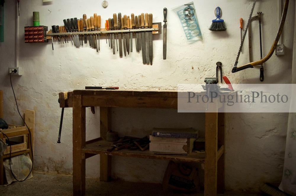 Laboratorio in cui l'artigiano lavora il legno di ulivo per ottenere utensili da cucina.Un particolare del banco da lavoro