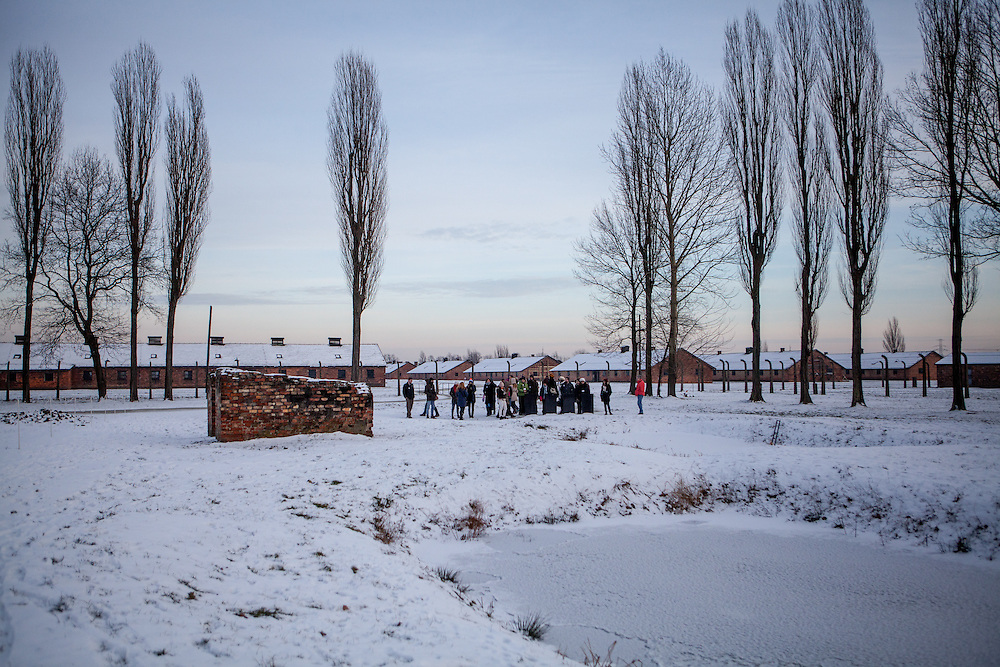 "aGroup of visitors beside the ruins of one of the crematoriums of Auschwitz II/Birkenau where lies a pond with 4 gravestones with the inscription in 4 different languages: ""To the memory of the men, women, and children who fell victim to the Nazi genocide. In this pond lie their ashes.  May their souls rest in peace.""."