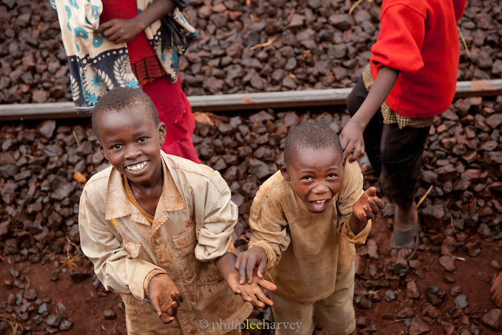 Young boys play on the rails as a train stops at a station on its way to Nairobi, Kenya