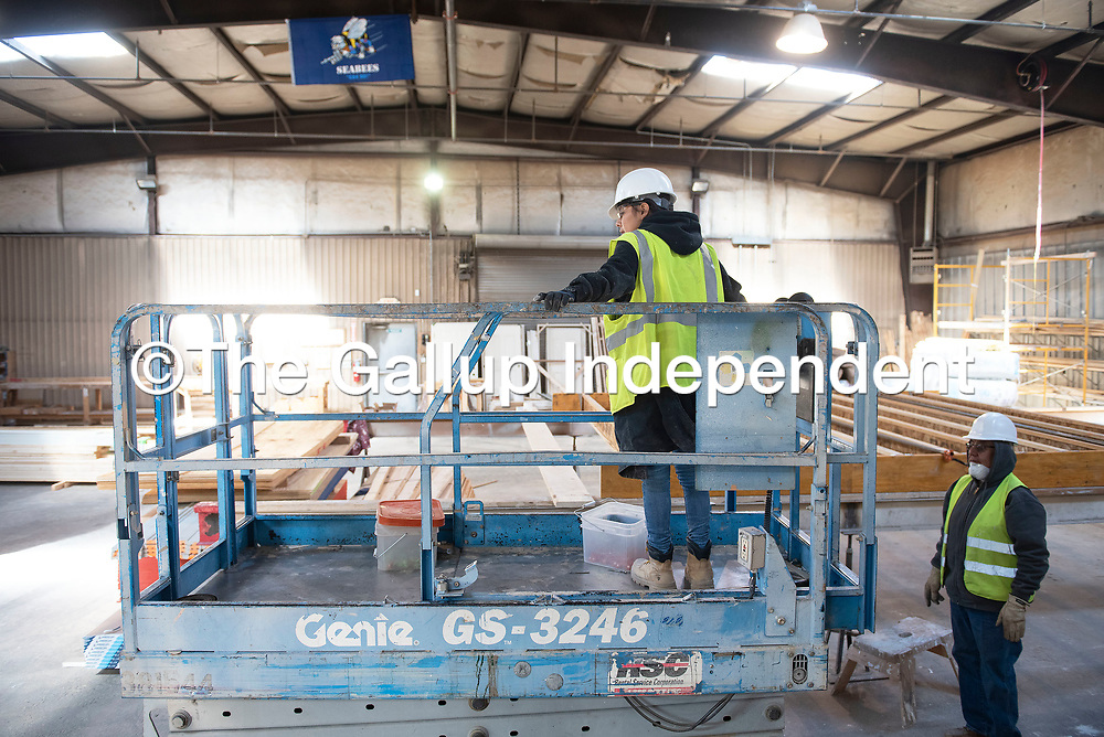 Naomi Begaye drives a mobile arial work platform as she gets directions from construction assistant Albert Benally, right, Tuesday afternoon at Greater Gallup Economic Development Corporation's workforce program in Gallup.