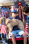 A boy wearing patriotic clothes rides on the back of a golf cart float with his dog during the annual Independence Day parade July 4, 2019 in Sullivan's Island, South Carolina. The tiny Sea Island beach community across from Charleston, was once a quarantine station for enslaved Africans, and is now one of the most affluent, least diverse communities with one of highest per capita real estate costs in the United States.