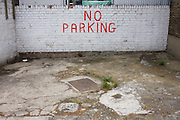 A No Parking sign hand-painted on to a whitened brick wall tells car drivers not to park on this private space in South London.