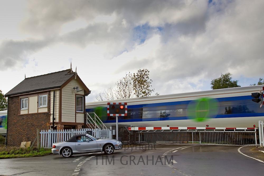 Car waits at railway crossing in Ascott-Under-Wychwood, Oxfordshire, United Kingdom