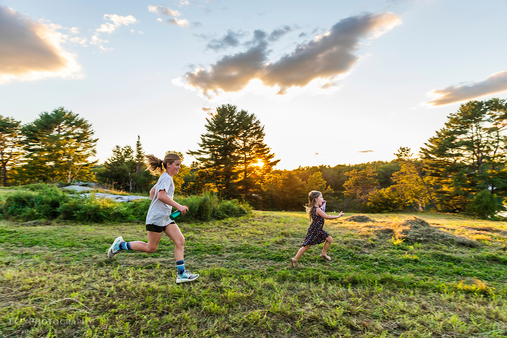 Girls running in a field as the sun sets at the Woodward Point Preserve in Brunswick, Maine.