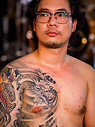 28 OCTOBER 2018 - BANGKOK, THAILAND:A man waits to go on stage during judging of the Realistic division at the 2018 MBK Center Tattoo Fest. Tatoo artists from around the world came to participate in the festival, which featured both modern (using tattoo machines) and traditional methods (done by hand with long needles) of tattooing.     PHOTO BY JACK KURTZ