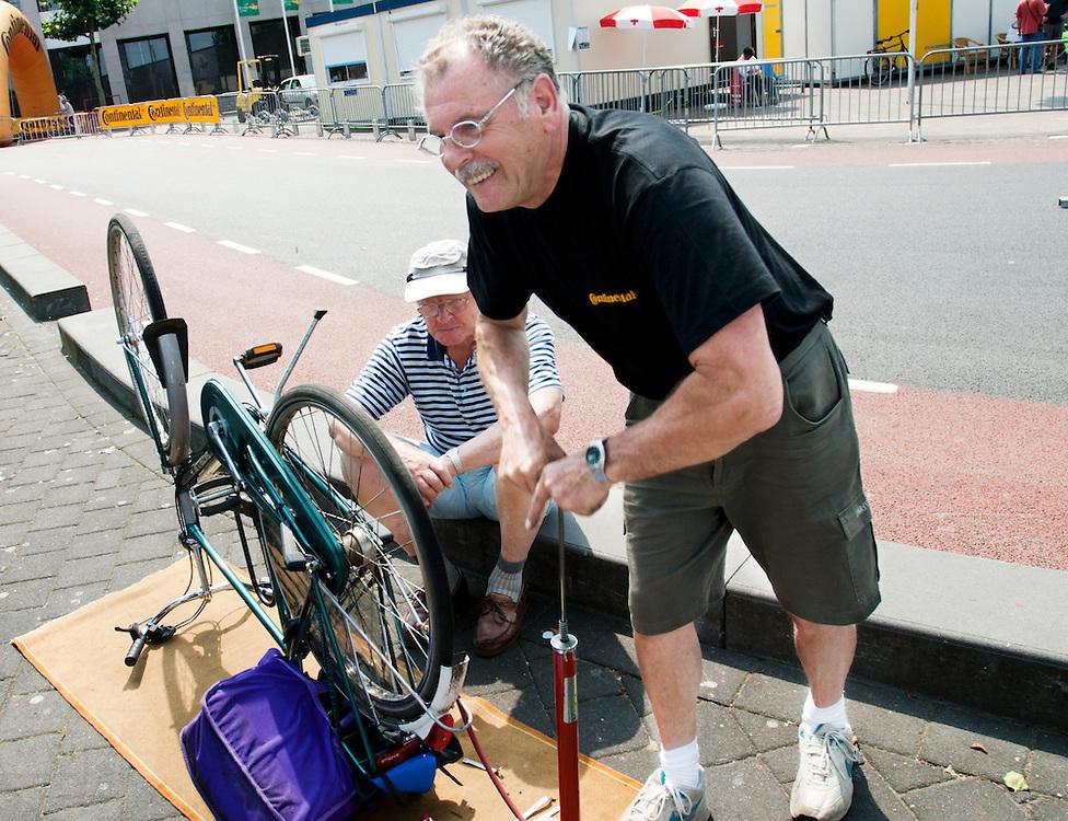 Een fietsenmaker plakt de band van een deelnemer aan de Nijmeegse fietsvierdaagse.<br /> <br /> A man is repairing a flat tyre.