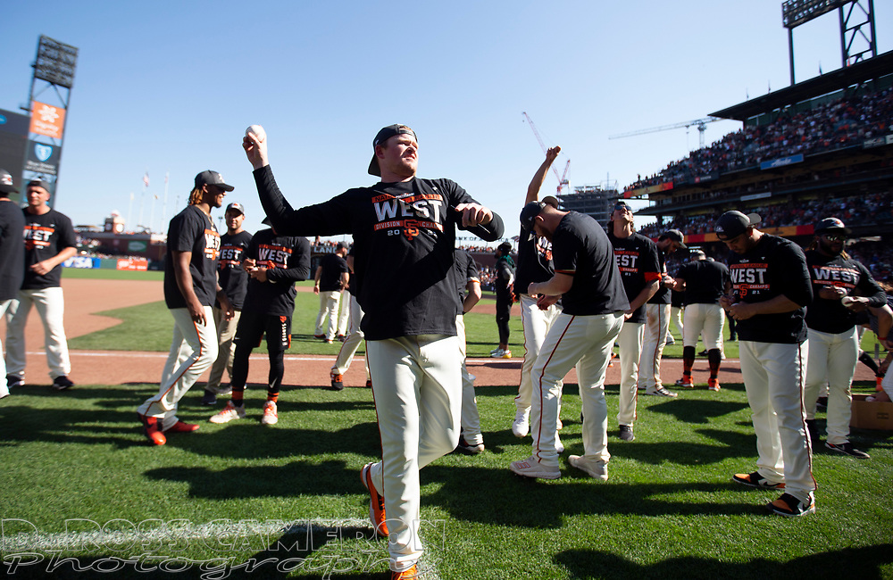 Oct 3, 2021; San Francisco, California, USA;  San Francisco Giants starting pitcher Logan Webb lobs baseballs to the fans in the stands as the team celebrates their 11-4 victory over the San Diego Padres at Oracle Park. The Giants clinched the National League West Division with the win. Mandatory Credit: D. Ross Cameron-USA TODAY Sports