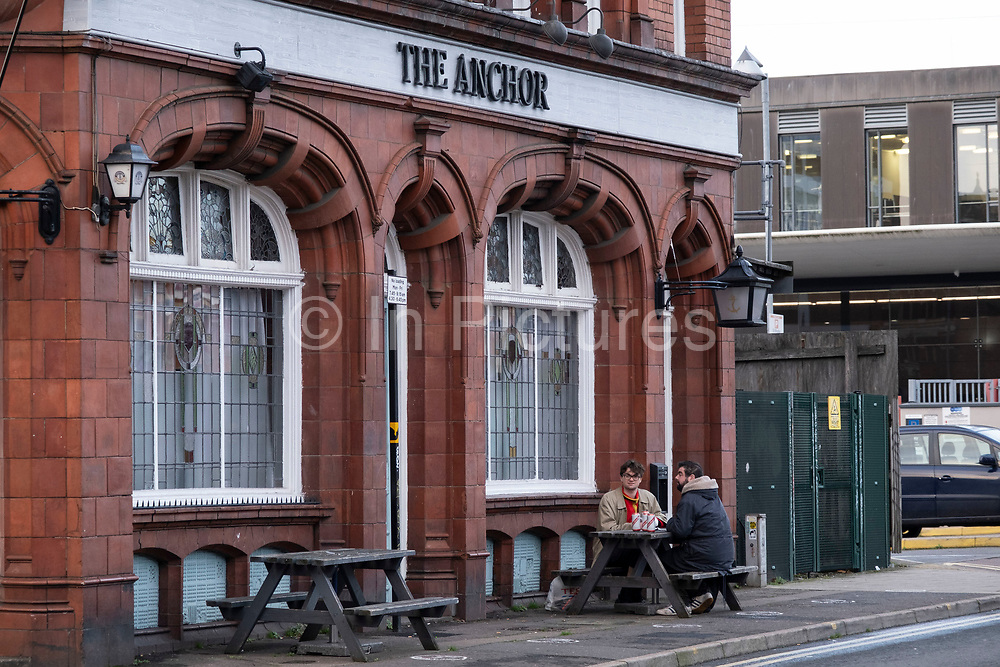 People drinking cans of beer outside the old red brick Anchor Inn pub in Digbeth which is currently closed due to tier three coronavirus restrictions on 14th December 2020 in Birmingham, United Kingdom. The national lockdown and following tier three status is a huge blow to the economy and for individual businesses in Britains second city, who were already struggling after eight months of Covid-19 restrictions. In tier 3 people can only meet other households in outdoor public spaces like parks, where the rule of six applies.