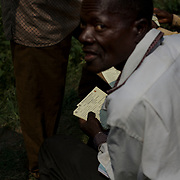 An unidentified man goes through the registration cards of voters at a polling station in Kinama neighbourhood, Bujumbura, June 29, 2015.