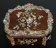 Arthur Gilbert succeeded in purchasing this snuffbox with diamond flowers from the N.Y. jeweller Harry Winston but only after he had bought a set of yellow diamonds to establish himself as an important customer.  The scene carved in hardstones on the base is adapted from a painting by Jean Baptiste Oudry (1686-1755) of a water spaniel and a swan, the latter replaced with a colourful mallard.