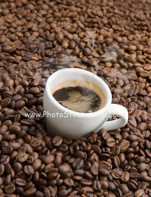 Hot Espresso coffee surrounded with coffee beans