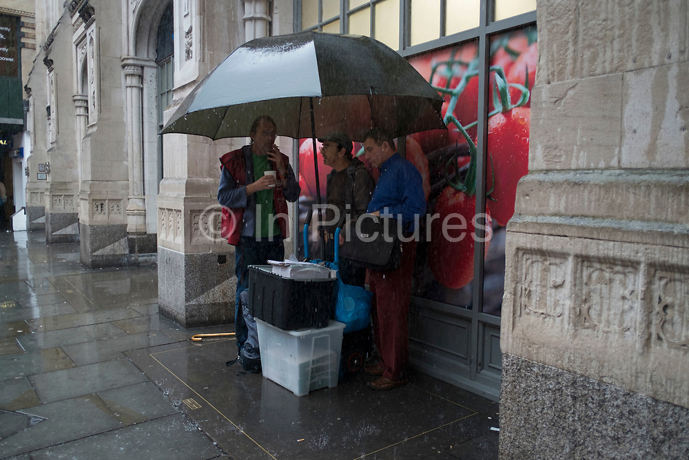 People running for cover or sheltering under umbrellas street scene in the heavy rain on Bishopsgate in the City of London, England, United Kingdom.