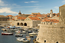 Europe, Croatia, Dalmatia, Dubrovnik.  Old city walls (built 10th century),Reveline fort (16th c.), red terracotta tile roofs, Cathedral dome, and marina. The historic center of Dubrovnik is a UNESCO World Heritage site.