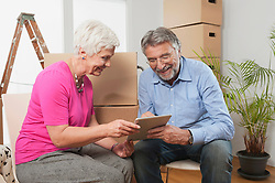 Senior couple using a digital tablet in new apartment, Bavaria, Germany