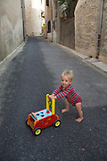 1 year old boy walking with a stroller in the empty street, 19th July 2015, Lagrasse France.