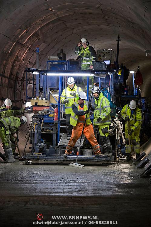 Met een snelheid van ongeveer 60 meter per dag is de zogenoemde Pavermachine op dit moment volop bezig beton te storten in de tunnel van de Noord/Zuidlijn tussen Rokin en CS. Daarmee wordt een volgende fase van de Noord/Zuidlijn steeds zichtbaarder, namelijk de afbouw en de voorbereidingen voor het leggen van de rails. In de ronde, eerder geboorde, Noord/Zuidlijn-tunnels kunnen geen metrosporen worden neergelegd zonder onderlaag. De relatief krappe tunnels verhinderen echter dat er standaardmachines aan het werk kunnen, dus heeft afbouwaannemer VIA NoordZuidlijn speciaal voor deze tunnels een aangepaste Paver ontwikkeld, die zich met zijn gekantelde rupsbanden tegen de tunnelwanden aan kan voortbewegen en tegelijkertijd onder zich een laag ongewapend beton kan storten.