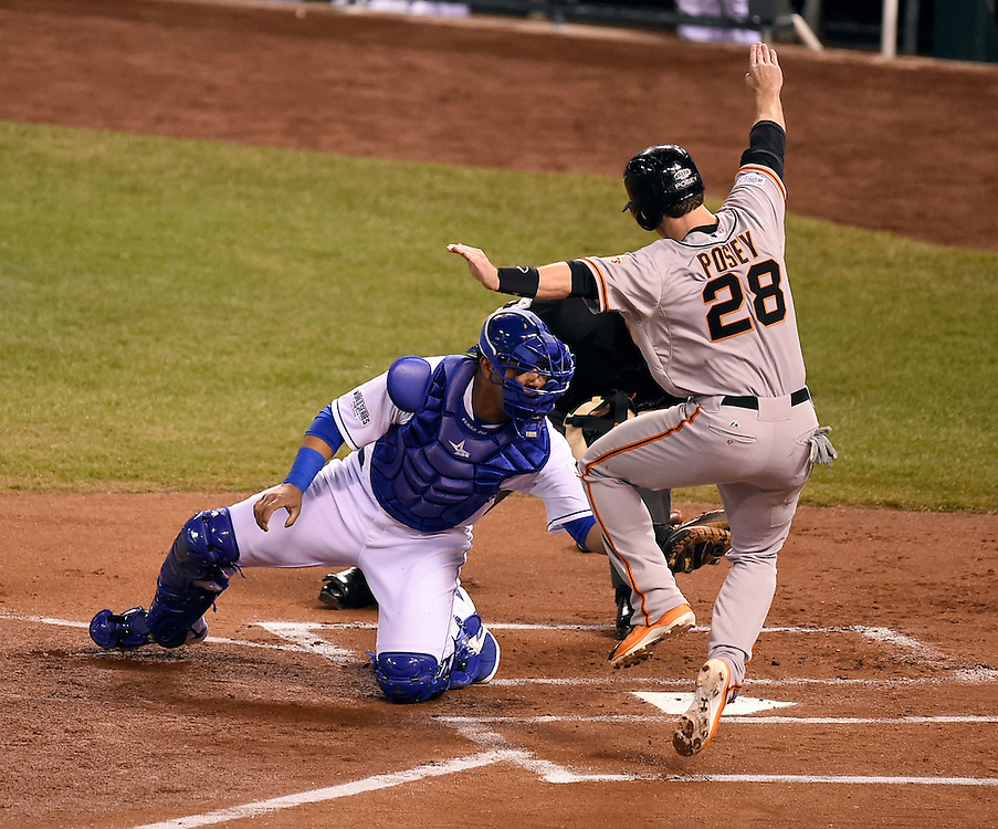 San Francisco Giants catcher Buster Posey was tagged out at home by Kansas City Royals catcher Salvador Perez in the first inning after Posey was hit in by a double by San Francisco Giants third baseman Pablo Sandoval during Game 1 of the World Series on Tuesday, October 21, 2014, at Kauffman Stadium in Kansas City, Mo. Perez prevented one run but another Giants runner scored on the play to give the Giants a 1-0 lead.