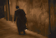 A priest walks past old buildings in a small Italian city