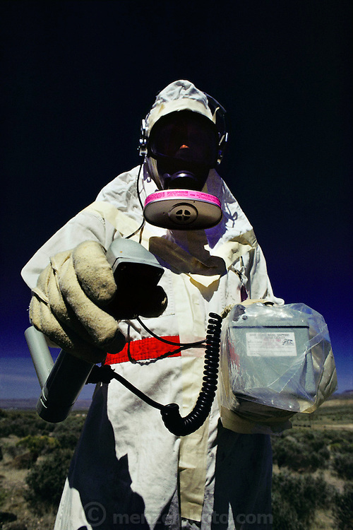 "A Defense Department specialist in a radiation suit on the Nuclear Test Site in the Nevada desert outside Las Vegas holds a Geiger counter during a simulated nuclear weapons accident test. In the ""Broken Arrow"" (any accident involving a nuclear weapon) exercise, the Defense Department and the Department of Energy simulated the crash of a helicopter carrying nuclear weapons. Various agencies and departments then practiced coordinating their responses in an effort to find and clean up the mess. Real radioactive material was spread around the desert and a large number of soldiers simulated the angry residents of a nearby town..1981"