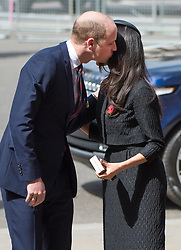 Meghan Markle, wearing a black Emilia Wickstead jacket and skirt and a Philip Treacy hat, is greeted  with a kiss by Prince William, Duke of Cambridge as they attend the Anzak Day service at Westminster Abbey in London on April 25, 2018.