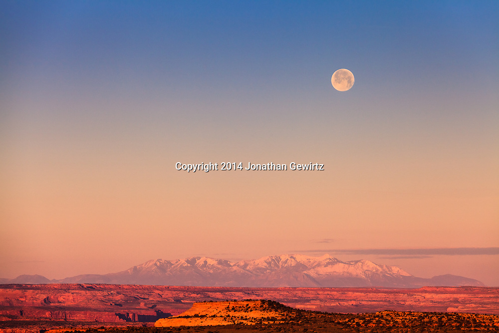 The full moon sets at sunrise over Utah's Canyonlands National Park and the Green River plateau, with Mount Pennell and Capitol Reef National Park in the distant background. WATERMARKS WILL NOT APPEAR ON PRINTS OR LICENSED IMAGES.<br /> <br /> Licensing: https://tandemstock.com/assets/92329233