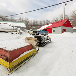 Snowmobiles are used to transport people and supplies around the LaRiviere family sugarbush in Big Six Township, Maine. The sugarhouse is in the background. Overhead lines are not electrical wires, but tubing carrying sap from the subarbush to the sugarhouse.
