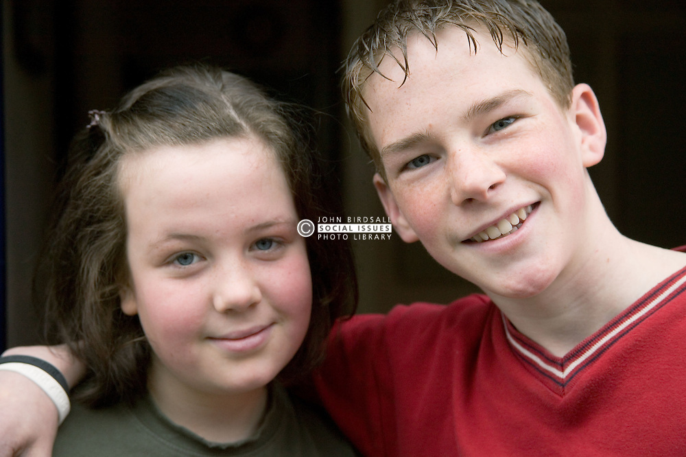 Brother and sister; arm in arm; smiling,