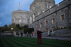 Residents at Windsor Castle, as it is turned blue to salute local heroes during Thursday's nationwide Clap for Carers NHS initiative to applaud NHS workers fighting the coronavirus pandemic when landmarks across the UK will be lit blue.