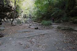 25 September 2012:   Illinois scenery near Oglesby and Ottawa..Matthiessen State Park.  A hiker walks along a upper dells path in a creek beed that in most years would be full of water. The drought of 2012 makes this alternate path available.