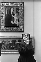 1982, Paris, France --- A Catholic nun contemplates artworks in a gallery of Italian Renaissance paintings at the Musee du Louvre. --- Image by © Owen Franken/CORBIS