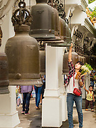 """12 JULY 2014 - PHRA PHUTTHABAT, SARABURI, THAILAND: People ring prayers bells before the Tak Bat Dok Mai at Wat Phra Phutthabat in Saraburi province of Thailand. Wat Phra Phutthabat is famous for the way it marks the beginning of Vassa, the three-month annual retreat observed by Theravada monks and nuns. The temple is highly revered in Thailand because it houses a footstep of the Buddha. On the first day of Vassa (or Buddhist Lent) people come to the temple to """"make merit"""" and present the monks there with dancing lady ginger flowers, which only bloom in the weeks leading up Vassa. They also present monks with candles and wash their feet. During Vassa, monks and nuns remain inside monasteries and temple grounds, devoting their time to intensive meditation and study. Laypeople support the monks by bringing food, candles and other offerings to temples. Laypeople also often observe Vassa by giving up something, such as smoking or eating meat. For this reason, westerners sometimes call Vassa """"Buddhist Lent.""""<br />     PHOTO BY JACK KURTZ"""