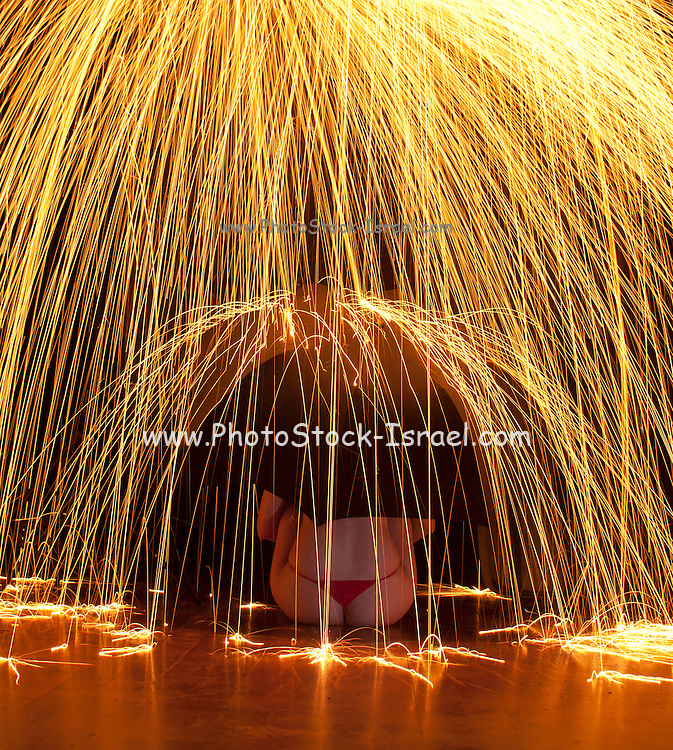 Woman with umbrella sits under a downpour of sparks