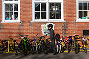 Young school boy parking his bike on the stand in the playground of South Farnborough Infant School, Hampshire, UK. Many children arrive by bicycle to school which is an eco school and runs many projects to save energy and sustainable living and has won an Ashden award for its work.