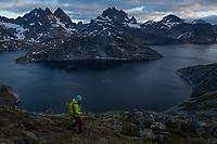 Female hiker hiking through mountain landscape rising above lake Solbjørnvatn, Moskenesøy, Lofoten Islands, Norway