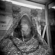 """A figure of """"Santa Muerte,"""" the saint who personifies death, lays inside an altar wearing a  a bridal gown and a face mask in Mexico City's Doctores neighberhood, on Apr. 17, 2020."""