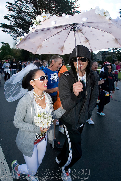 Linda Le, left, and Long Hong, both of Sunnyvale, Calif., know that rain on your wedding day is supposed to be good luck as they take cover under an umbrella on Fell Street during the 100th running of the Bay to Breakers 12K through San Francisco, Sunday, May 15, 2011. (Photo by D. Ross Cameron)