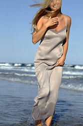 woman in a long dress enjoying a walk in the ocean