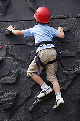 Young boy on a climbing wall part of a transformer vehicle; activities run by youth work services at the Newstead Tree Fest,